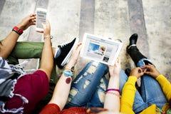 Estudiantes universitarios que usan concepto de los dispositivos de Digitaces imagen de archivo