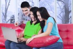 Estudiantes universitarios que usan el ordenador portátil en casa Imagenes de archivo