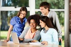 Estudiantes universitarios que usan el ordenador portátil en el escritorio adentro Fotografía de archivo