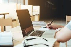 Estudiantes universitarios que usan el ordenador portátil para la preparación de la investigación en colleg Imagen de archivo