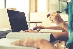 Estudiantes universitarios que usan el ordenador portátil para la preparación de la investigación en colleg Imagen de archivo libre de regalías