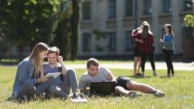 Estudiantes universitarios que usan el ordenador portátil y la tableta en césped almacen de video