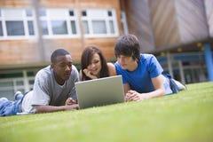 Estudiantes universitarios que usan la computadora portátil en césped del campus Imagenes de archivo