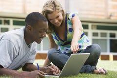 Estudiantes universitarios que usan la computadora portátil en césped del campus Fotos de archivo libres de regalías