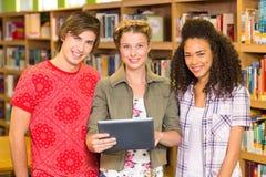 Estudiantes universitarios que usan la tableta digital en biblioteca Fotos de archivo