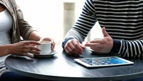 Estudiantes universitarios que usan la tableta en el café del campus metrajes