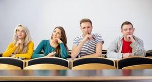 Estudiantes universitarios sonrientes pensativos en sala de clase Fotografía de archivo