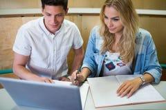 Estudiantes universitarios sonrientes que usan el ordenador portátil Foto de archivo libre de regalías