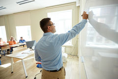 Estudiantes y escritura del profesor en el tablero blanco de la escuela Fotografía de archivo