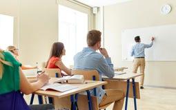 Estudiantes y escritura del profesor en el tablero blanco de la escuela Foto de archivo