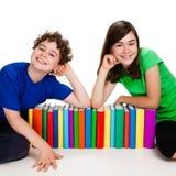 Estudiantes y pila de libros Imágenes de archivo libres de regalías