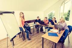 Estudiantes y profesor cansados en sala de clase Imagen de archivo