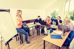 Estudiantes y profesor cansados en sala de clase Imagenes de archivo