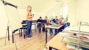 Estudiantes y profesor cansados en sala de clase Imagen de archivo libre de regalías