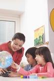 Estudiantes y profesor Looking en el globo Fotografía de archivo