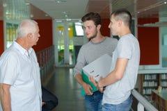 Estudiantes y profesor Walking Along Hallway de la High School secundaria imagen de archivo