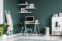 Estudie el espacio para un adolescente en un interior verde oscuro del dormitorio con Foto de archivo