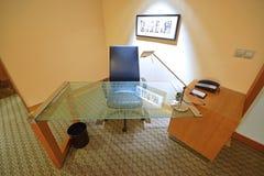Estudie la tabla hecha del vidrio moderado con la silla de cuero Imagen de archivo libre de regalías