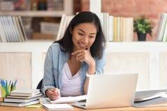Estudio asiático sonriente de la estudiante en biblioteca con los libros del ordenador portátil imagen de archivo libre de regalías