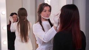 Estudio de la belleza El cosmetólogo, dibuja las cejas de una muchacha antes del procedimiento del maquillaje permanente 4K MES l almacen de video