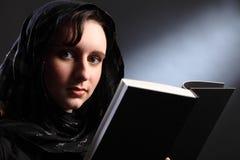 Estudio de la biblia para la mujer joven religiosa en pañuelo Fotografía de archivo