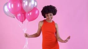 Estudio de la mujer joven aislado en día rosado del ` s de las mujeres en el vestido rojo que sostiene los globos