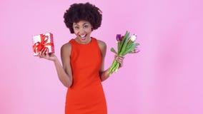 Estudio de la mujer joven aislado en día rosado del ` s de las mujeres en el vestido rojo que sostiene tulipanes y el regalo