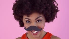 Estudio de la mujer joven aislado en mueca rosada del día del ` s de las mujeres usando el bigote de papel metrajes