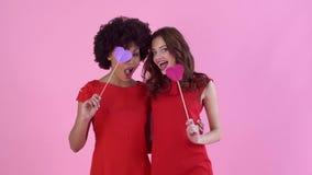Estudio de las mujeres jovenes aislado en el día rosado del ` s de las mujeres que sostiene los palillos con los corazones de pap metrajes