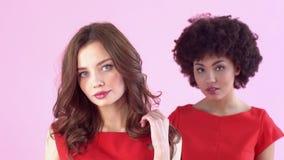 Estudio de las mujeres jovenes aislado en la presentación rosada del día del ` s de las mujeres confiada metrajes