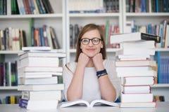 Estudio del estudiante en biblioteca, usando la tableta y la búsqueda para Imagen de archivo libre de regalías