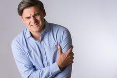 Estudio del hombre maduro que agarra el brazo como advertencia del ataque del corazón Imagen de archivo