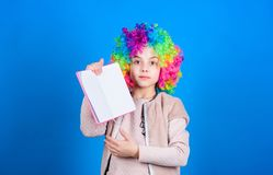 Estudio duro Historia ridícula Lectura del libro divertido Club de la literatura Las bromas reservan concepto Peluca rizada color imagen de archivo