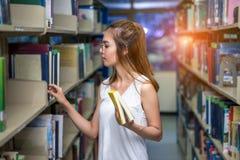 Estudio joven del libro del hallazgo del asiático de la muchacha del estudiante foto de archivo libre de regalías