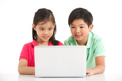 Estudio tirado de dos niños chinos con la computadora portátil Imagen de archivo
