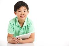 Estudio tirado de muchacho chino con la tablilla de Digitaces Fotos de archivo