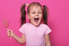 Estudio tirado de poca boca atractiva de la abertura del niño extensamente, mirando directamente la cámara con el entusiasmo, sos imágenes de archivo libres de regalías