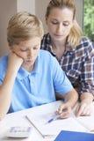 Estudios caseros femeninos de Helping Boy With del profesor particular Imagen de archivo libre de regalías