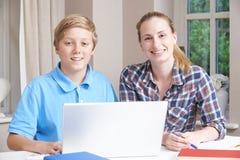 Estudios caseros femeninos de Helping Boy With del profesor particular usando el ordenador portátil Foto de archivo