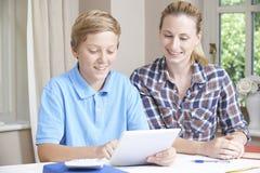 Estudios caseros femeninos de Helping Boy With del profesor particular usando la tableta de Digitaces Fotografía de archivo