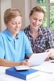 Estudios caseros femeninos de Helping Boy With del profesor particular usando la tableta de Digitaces Foto de archivo libre de regalías