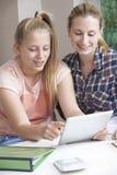 Estudios caseros femeninos de Helping Girl With del profesor particular usando la tableta de Digitaces Foto de archivo
