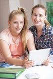 Estudios caseros femeninos de Helping Girl With del profesor particular usando la tableta de Digitaces Fotos de archivo
