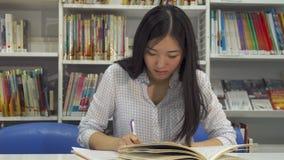 Estudios del estudiante en la biblioteca almacen de metraje de vídeo