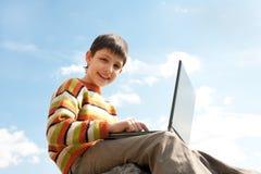 Estudios felices del cabrito usando una computadora portátil Imagen de archivo