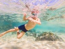 Estudo de natureza subaquático, menino que mergulha no mar azul claro imagem de stock royalty free