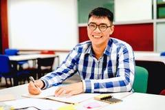 Estudo do estudante masculino no terreno | Sorrindo e fazendo trabalhos de casa Fotografia de Stock