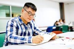 Estudo do estudante masculino no terreno | Sorrindo e fazendo trabalhos de casa Imagens de Stock Royalty Free