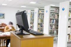 Estudo em uma biblioteca com computador Fotos de Stock Royalty Free
