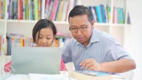 Estudos da menina com portátil e seu pai video estoque
